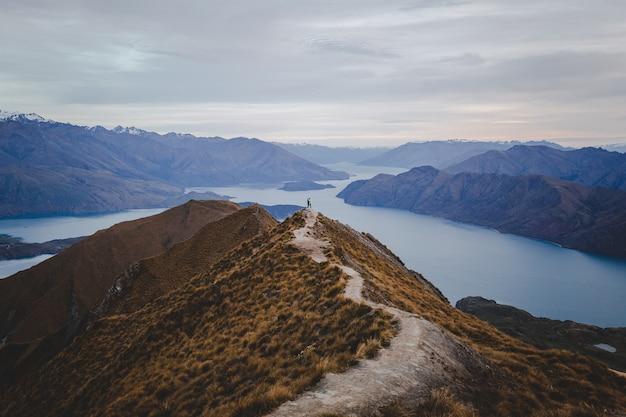 가벼운 Cloudscape 아래 거리에있는 산들과 뉴질랜드의 Roys Peak의 전경 무료 사진