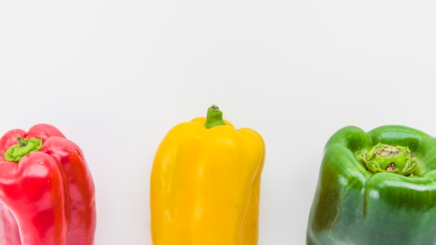 Panoramic view of red; yellow and green bell peppers on white surface Free Photo