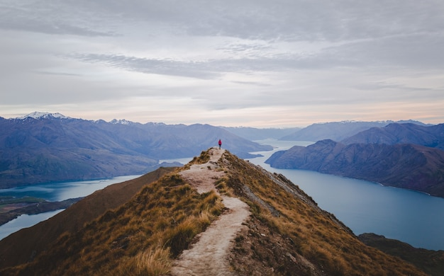 Panoramic view of the roys peak in new zealand with low mountains in the distance under cloudscape Free Photo