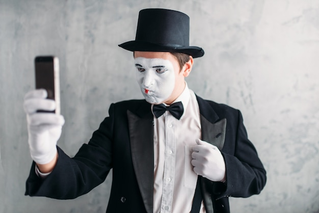 Pantomime actor with makeup mask makes selfie Premium Photo