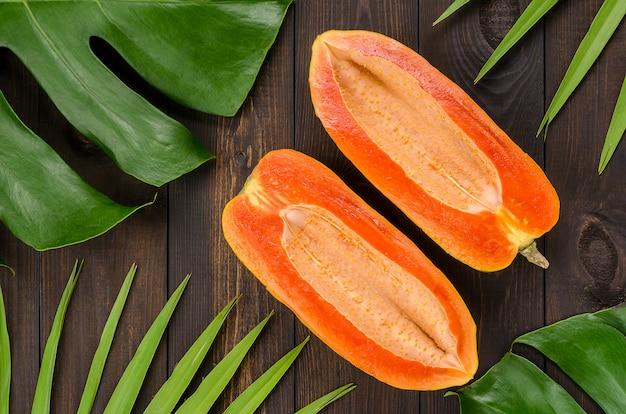 Papaya cut in half on a dark wooden background. Premium Photo