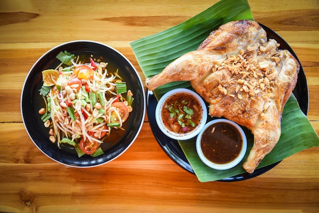 Papaya salad and grilled chicken with sauce served on plate on the wooden table som tum thai menu asian food Premium Photo