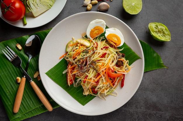 Салат из папайи, подается с рисовой лапшой и овощным салатом. украшен ингредиентами тайской кухни. Бесплатные Фотографии