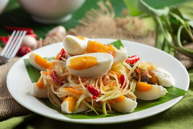 Insalata di papaya servita con spaghetti di riso e insalata di verdure decorata con ingredienti alimentari tailandesi. Foto Gratuite