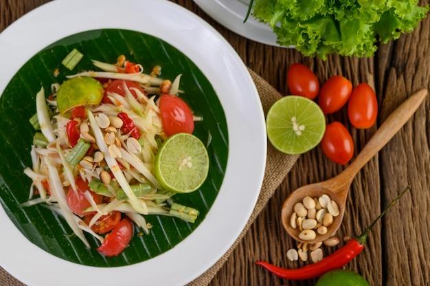 Insalata di papaia (som tum tailandese) su un piatto bianco su un tavolo di legno. Foto Gratuite