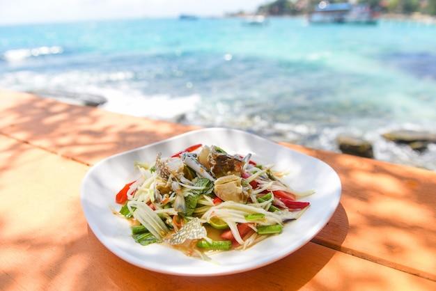 Салат из папайи с синим крабом на фоне морского побережья стола и пляжа / тайская еда сырые крабы пряный салат из морепродуктов и овощей на концепцию моря Premium Фотографии