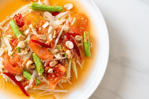 パパイヤスパイシーサラダ-ソムタム-タイの伝統的な屋台の食べ物のスタイル Premium写真