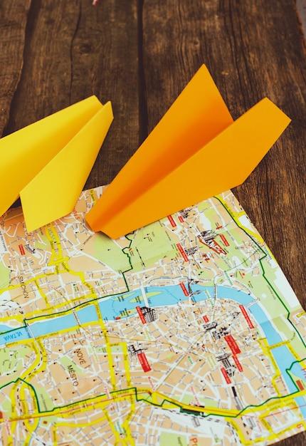 지도에 종이 비행기. 여행 컨셉 무료 사진