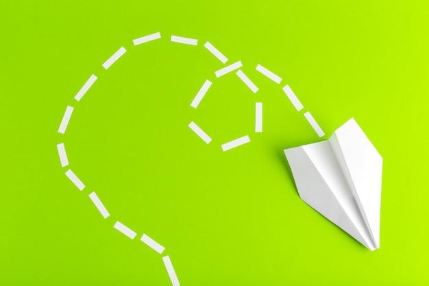 녹색 배경에 점선으로 연결 된 종이 비행기. 사업 프리미엄 사진