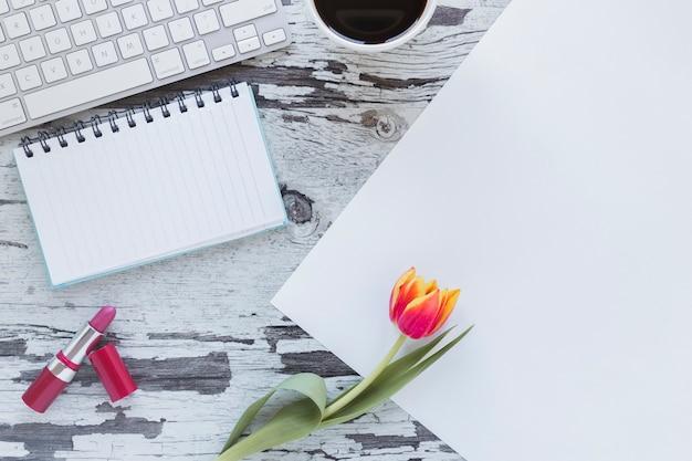 チューリップの花とキーボードのぼろぼろの机の近くの紙とノート 無料写真