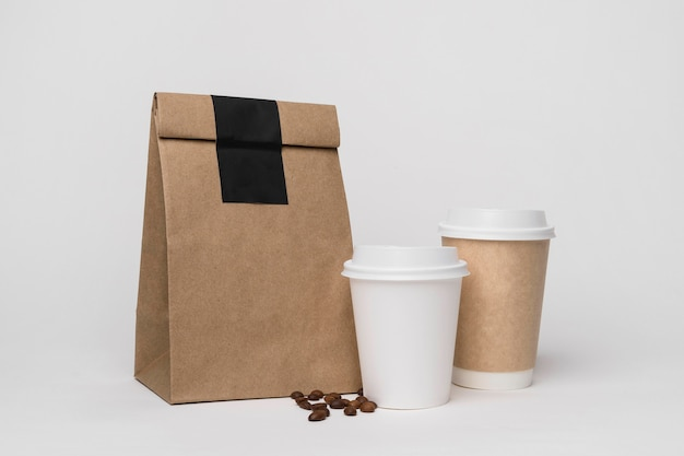Paper bag and coffee cups arrangement Free Photo