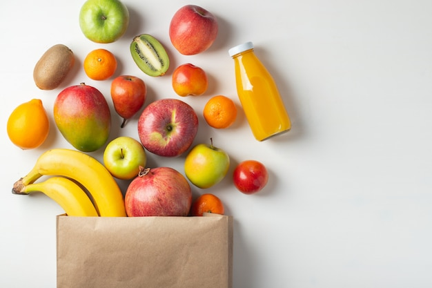 Paper bag of different health fruits on a table. Premium Photo