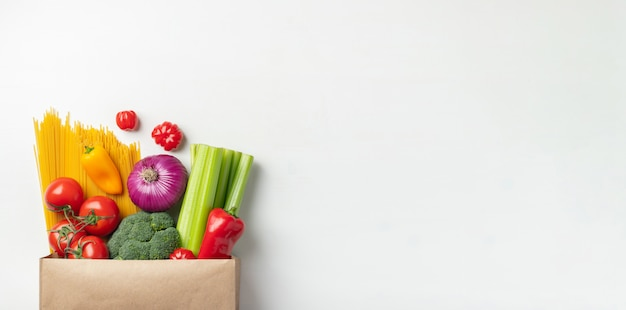 Paper bag of different healthy food on a table. Premium Photo