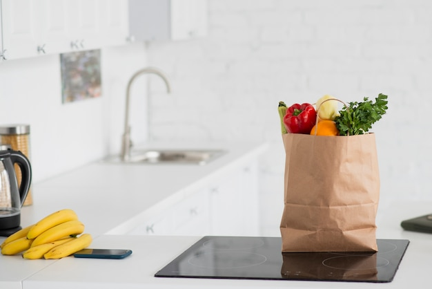 Paper bag full of vegetables set in kitchen Premium Photo