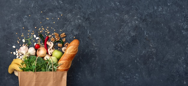 Paper bag vegetables and fruit on a dark with copy space top view. bag food concept Premium Photo