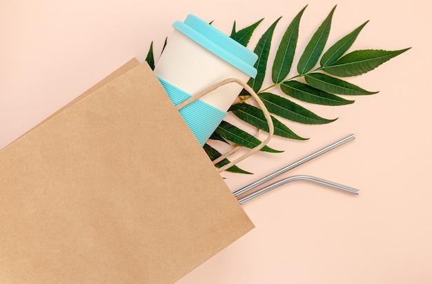 Бумажный пакет с бамбуковой чашкой и многоразовыми соломинками на розовом фоне Premium Фотографии