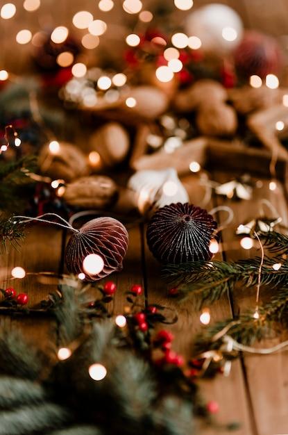 나무 테이블에 크리스마스 불빛 종이 공 화환 무료 사진