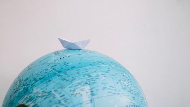 Paper boat on globe Free Photo