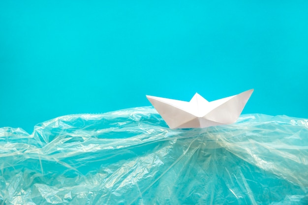 Paper boat in plastic water Free Photo