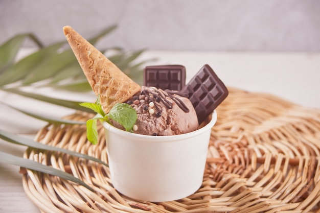 Paper bowl of chocolate ice cream with small waffle cone and chocolate Premium Photo