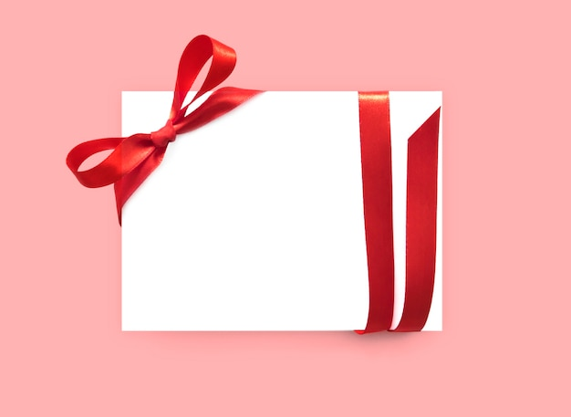 Paper card with red bow ribbon. Premium Photo