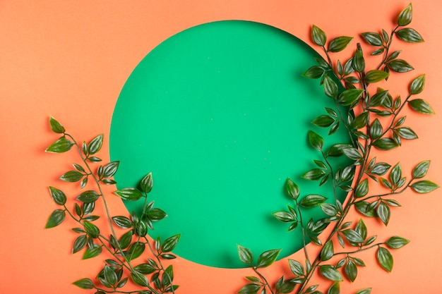 Paper circle design with leaves beside Free Photo