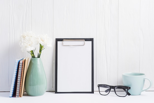 Paper on clipboard; vase; eyeglasses; cup; books and vase on white backdrop Free Photo