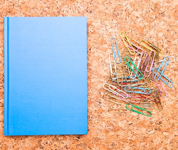 Paper clips and blue notebook on cork board Free Photo