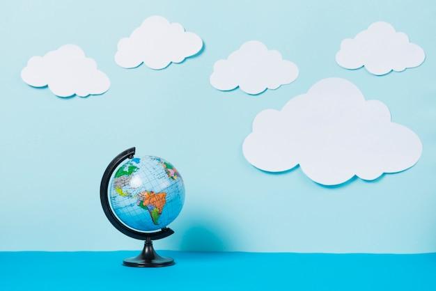 Paper clouds near globe Premium Photo