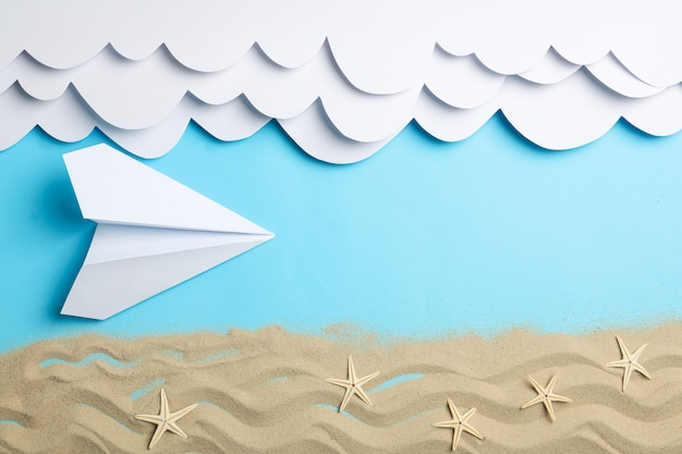 Paper clouds and plane, sand with starfishes on blue. vacation Premium Photo