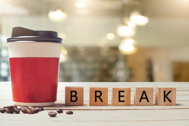 Paper coffee cup and  break wood letter with blurred coffee shop Premium Photo