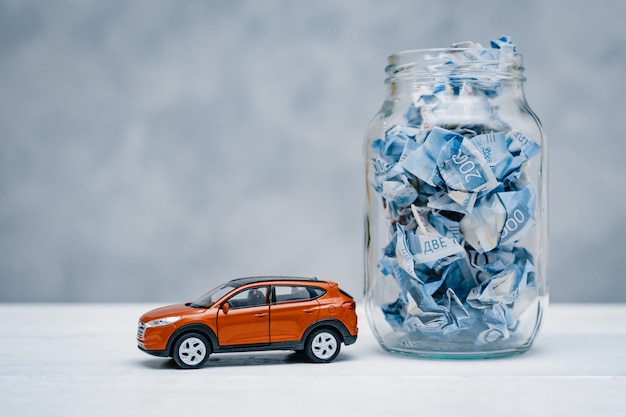 Paper crumpled money in a glass jar. concept of save money for a car Premium Photo