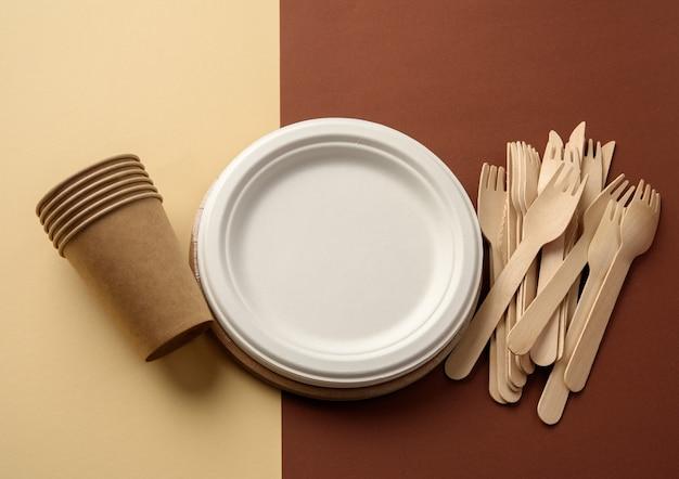 Бумажный стаканчик и деревянная вилка, пустая круглая одноразовая тарелка коричневого цвета из переработанных материалов на коричневой поверхности. концепция отсутствия неперерабатываемого мусора, отказ от пластика, вид сверху Premium Фотографии