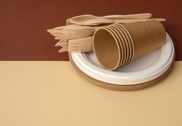 Бумажный стаканчик и деревянная вилка, пустая круглая одноразовая тарелка коричневого цвета из переработанных материалов на коричневой поверхности. концепция отсутствия неперерабатываемого мусора, отказ от пластика Premium Фотографии