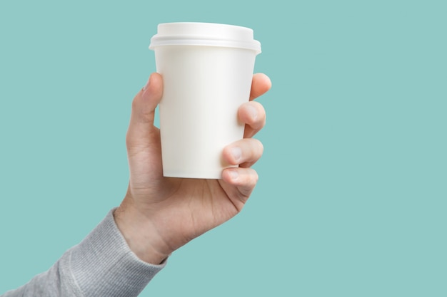 A paper cup of coffee in the hand. white paper cup of coffee in hand isolated Premium Photo