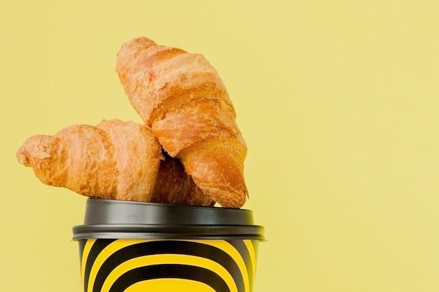 Бумажный стаканчик с кофе и круассанами на желтом. Premium Фотографии
