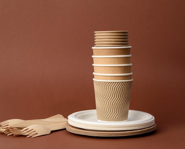 Бумажный стаканчик, белые тарелки и деревянные вилки и ножи на коричневой поверхности. концепция отказа от пластика, нулевые отходы Premium Фотографии