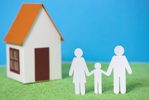 Paper cut of family with house on green grass background Premium Photo