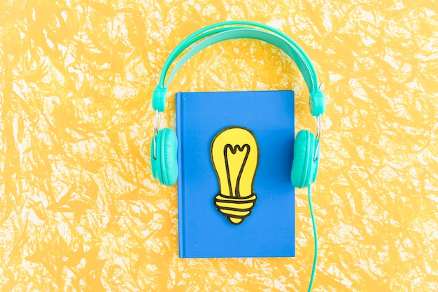 Paper cut out yellow light bulb on closed notebook with headphone on textured background Premium Photo