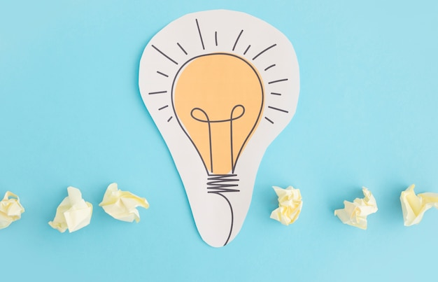 Paper cutout of light bulb with crumpled paper on blue background Free Photo