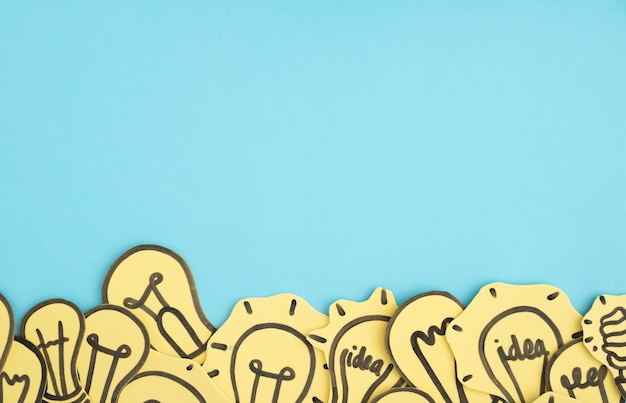 Paper cutout light bulbs on blue background Free Photo