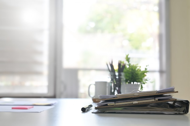 Paper document files and pen business equipment on office table and window light. Premium Photo