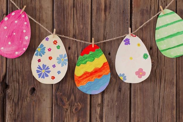 Бумага пасха крашеные яйца окрашены повесить на прищепки на фоне старые деревянные стены. Premium Фотографии