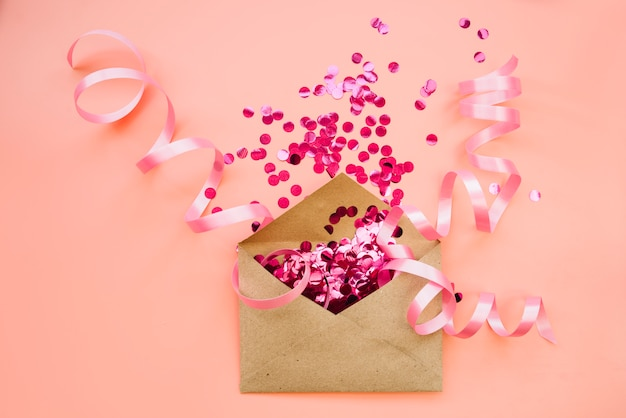 Paper envelope with pink confetti and ribbons Free Photo