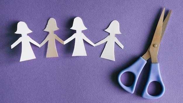 Paper female figures and scissors Free Photo