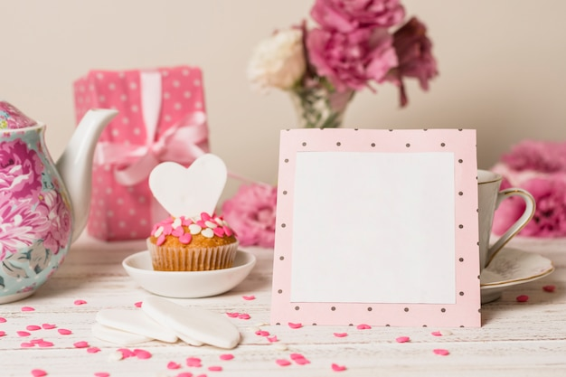 Paper frame near delicious cake, present box and teapot Free Photo