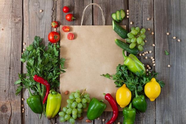 新鮮な野菜や果物の木製のテーブルの上の紙の買い物袋 Premium写真