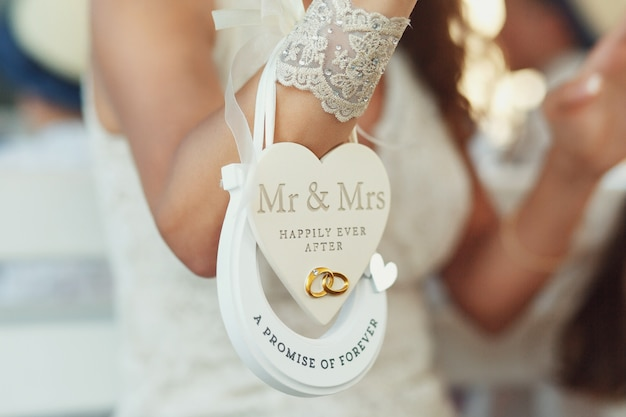 Paper heart 'mr & mrs happily ever after' and horseshoe 'a promise of forever' hang on bride's wirst Free Photo