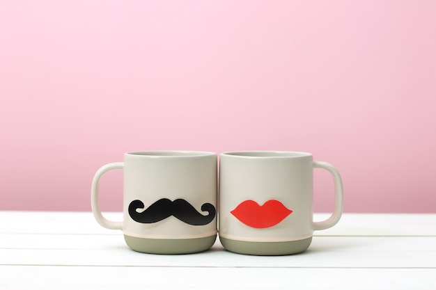 Paper heart shape fake lips and mustaches decoration on pink cup over white wooden table pink background. Premium Photo