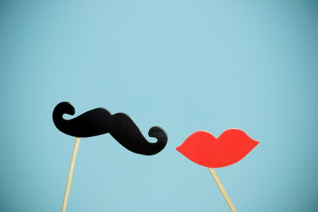 Paper heart shape fake lips and mustaches in sticks in front of blue background. Premium Photo